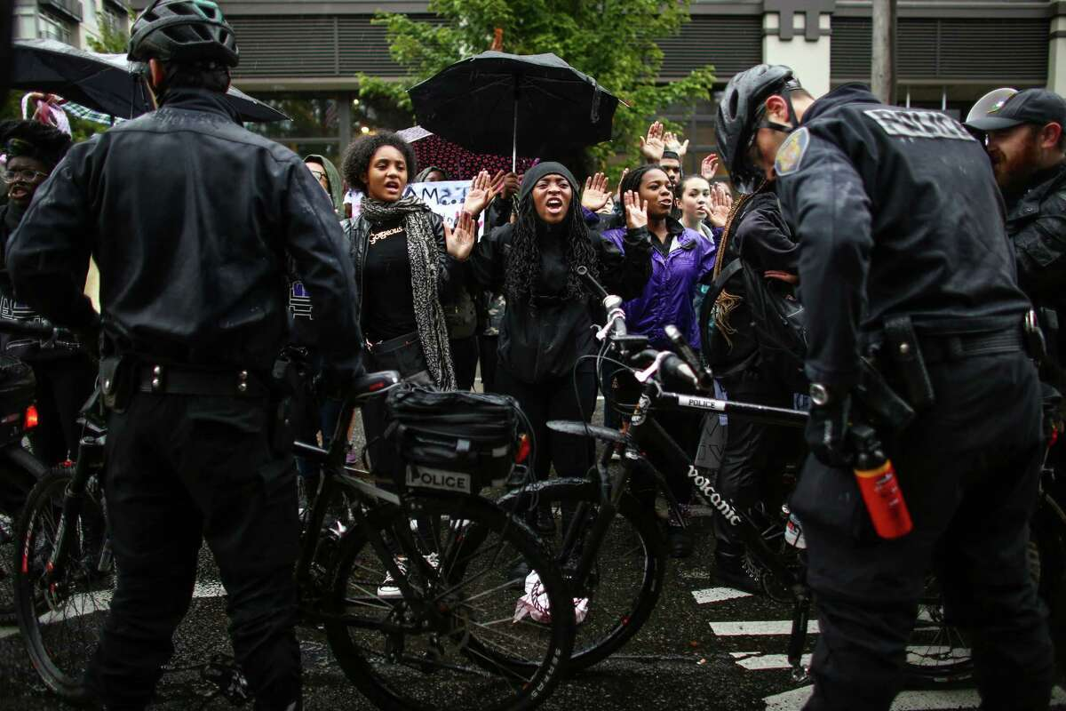 Students affiliated with the Garfield High School Black Student Union gather at the Seattle Police Department's East Precinct after a march there from the school. The young marchers were calling for an end to police brutality. Photographed on Wednesday, October 22, 2014.