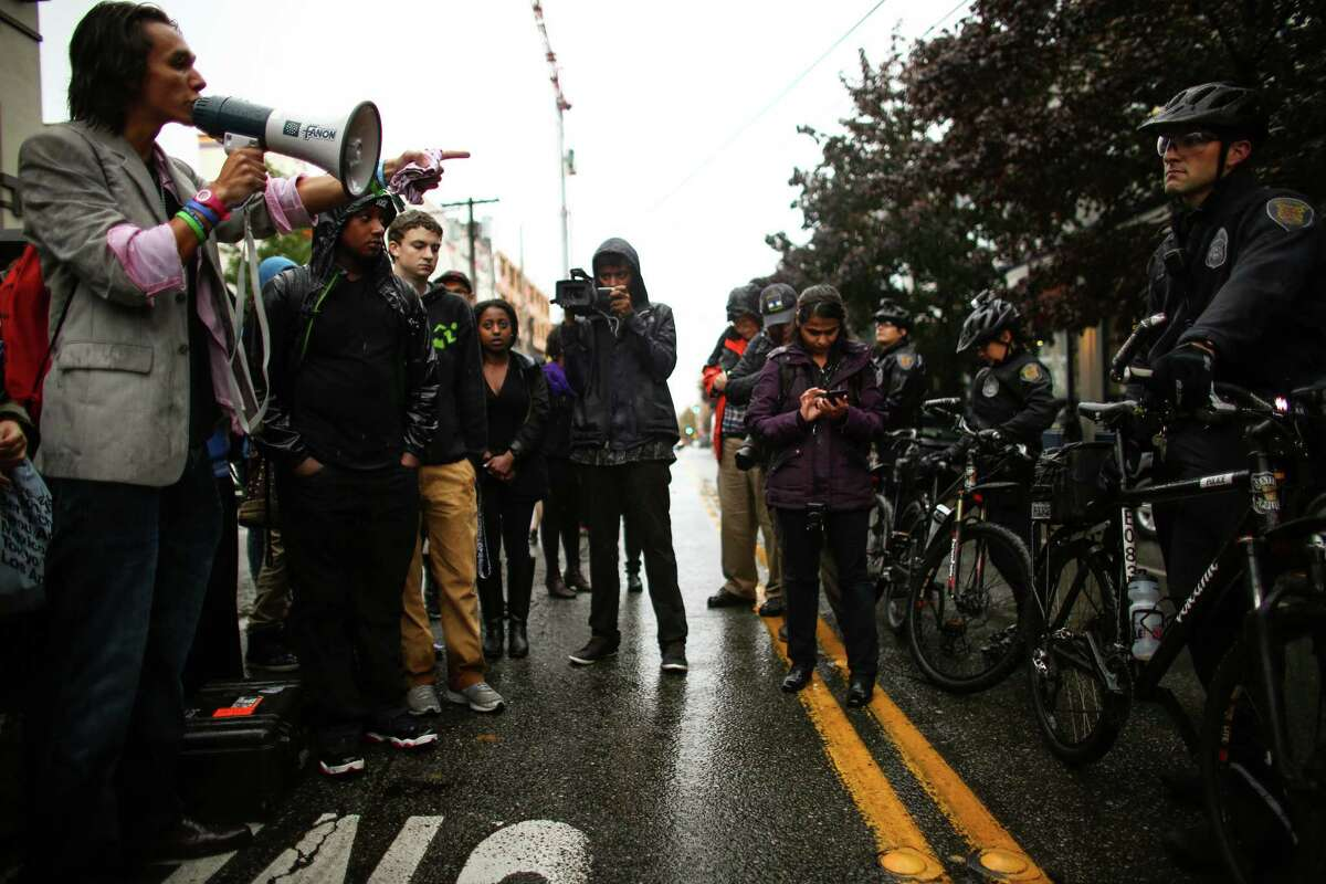 Students affiliated with the Garfield High School Black Student Union talk to officers through a megaphone at the Seattle Police Department's East Precinct after a march there from the school. The young marchers were calling for an end to police brutality. Photographed on Wednesday, October 22, 2014.