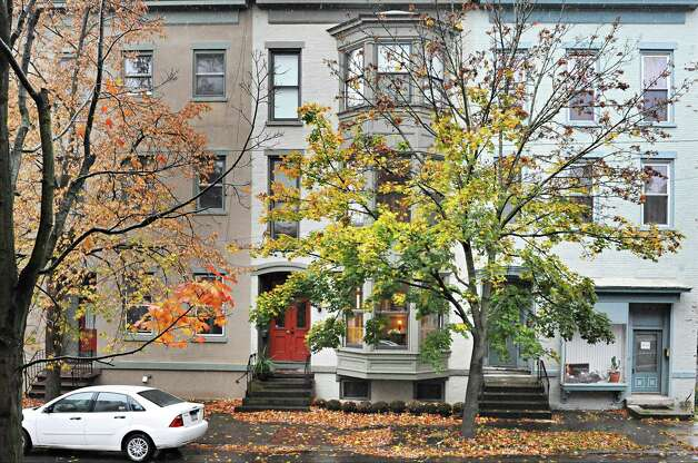 Sandra Rouse's newly purchased home at 159 First Street, center, Tuesday Oct. 21, 2014, in Troy, NY.  (John Carl D'Annibale / Times Union) Photo: John Carl D'Annibale / 00029127A