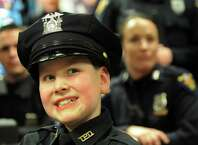 Honorary member J.P. Honsinger, 10, of Clifton Park, center, sits among fellow officers during roll on Friday, Jan. 31, 2014, at Troy Police Headquarters in Troy, N.Y. (Cindy Schultz / Times Union archive)