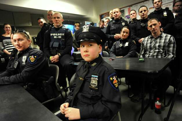 Honorary member J.P. Honsinger, 10, of Clifton Park, center, sits among fellow officers during roll on Friday, Jan. 31, 2014, at Troy Police Headquarters in Troy, N.Y. (Cindy Schultz / Times Union archive) Photo: Cindy Schultz / 10025581A
