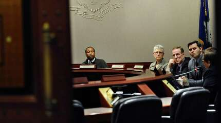 Scott Jackson, Chairman of the Sandy Hook Advisory Commission, center, listens as committee member Dr. Alice M. Forrester, right, speaks, during a meeting of the commission at the Legislative Office Building, Friday, Oct. 24, 2014, in Hartford, Conn.  Victims' parents scheduled to attend the meeting did not show.