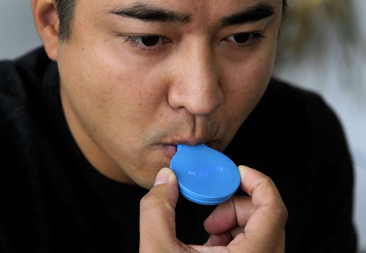 Charles Michael Yim, CEO of Breathometer, demonstrates how to use the new Breeze breath tester at the company's Burlingame headquarters. Below: the device with the smartphone app.