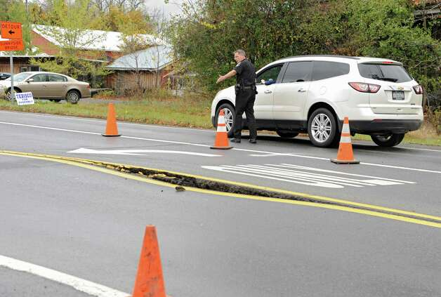 A police officer explains to a motorist why she has to turn around as Freemans Bridge Rd. between Dutch Meadows Ln & Maple Ave. is closed to traffic due to a water main break on Friday, Oct. 24, 2014, in Glenville, N.Y.  (Lori Van Buren / Times Union) Photo: Lori Van Buren / 00029199A