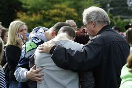 People embrace in a circle at a a church, Friday, Oct. 24, 2014, where students were taken to be reunited with parents following a shooting at Marysville Pilchuck High School in Marysville, Wash. (AP Photo/Ted S. Warren)