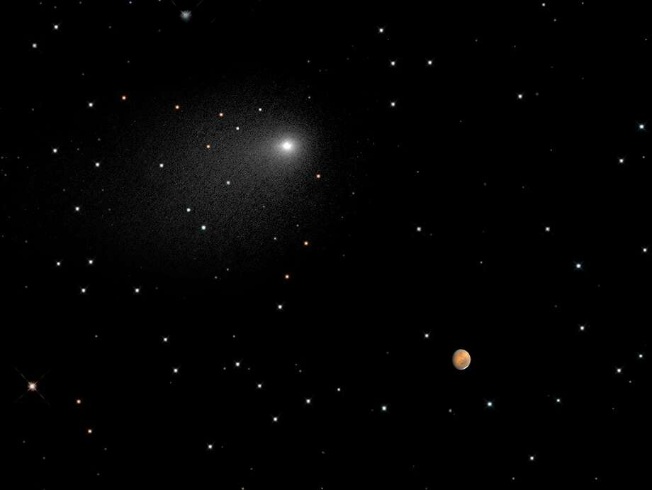 The comet Siding Spring passes Mars on Oct. 19, 2014, as shown in this composite NASA Hubble Space Telescope Image. Photo: NASA,  ESA,  PSI,  JHU/APL,  STScI/AURA