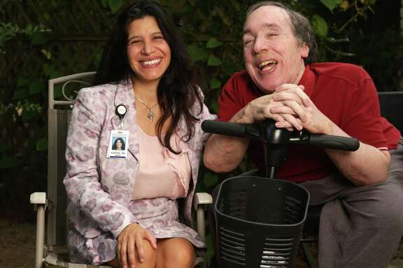 Dr. Sandra Gomez enjoys a moment with her patient Sanford Hughes at Hughes'  home in Spring. (Billy Smith II/Houston Chronicle)