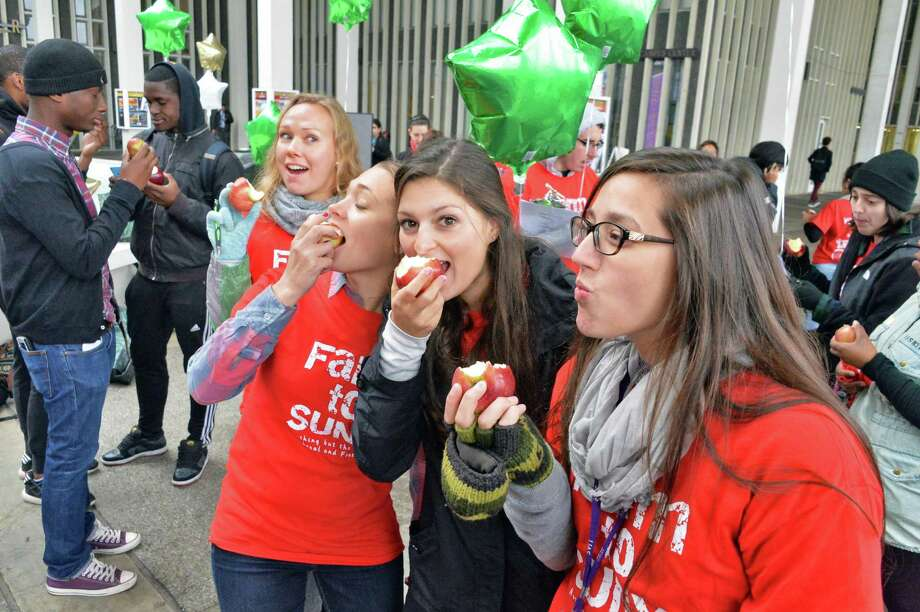 UAlbany students bite into apples during the inaugural NY Campus Crunch in which students on campuses across New York State will take a collective bite out of New York State apples on Food Day, Friday, October 24, 2014, in Albany, NY.  (John Carl D'Annibale / Times Union) Photo: John Carl D'Annibale / 00029172A