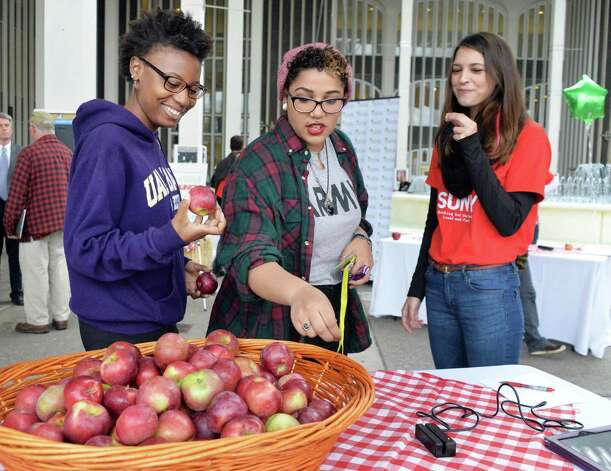UAlbany students, from left, Tiarra Jackson, Stephanie Collado and Nicholle Gregor during the inaugural NY Campus Crunch in which students on campuses across New York State will take a collective bite out of New York State apples on Food Day, Friday, October 24, 2014, in Albany, NY.  (John Carl D'Annibale / Times Union) Photo: John Carl D'Annibale / 00029172A
