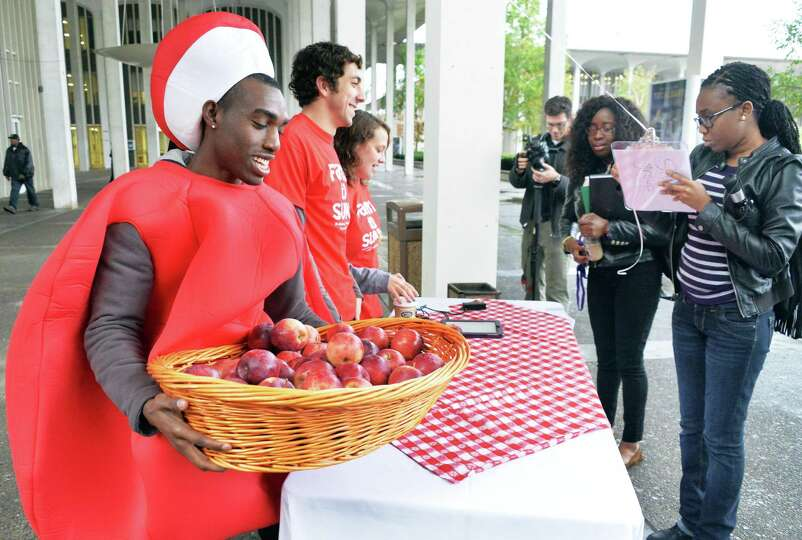 Dressed as a giant apple, UAlbany senior Sean Taylor of Farmingdale, NY,left, puts out a basket of a