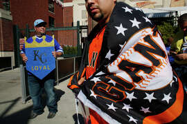 Jesse Tello of San Francisco shows his support for the Giants outside AT&T Park while Ron Johnson of Lafayette, hoping to buy a ticket, holds a sign backing the Royals before Game 3 of the World Series.
