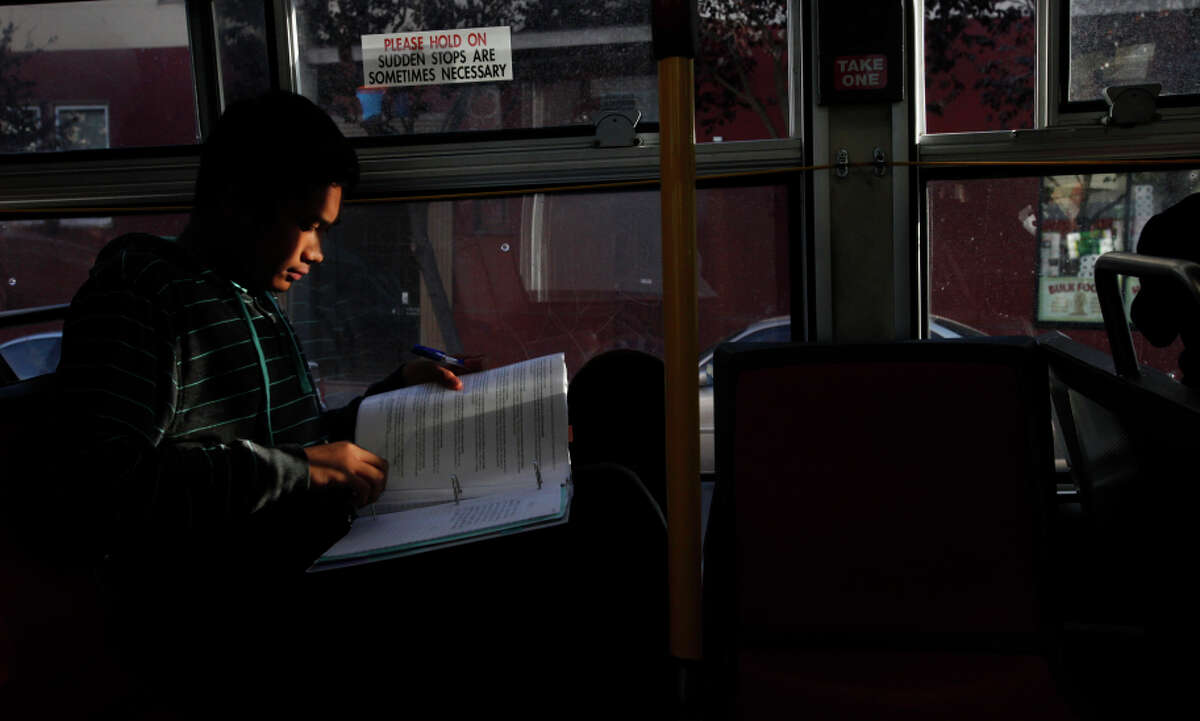 Byronne Rodrigo, 14, works on his homework while riding the bus home after school Oct. 23, 2014, in San Francisco. The Rodrigo family has been living in transitional housing for almost a year after staying with many family members in a small apartment. The family members haven't really had a place of their own and have enjoyed having the apartment to themselves but their time there is almost up. Byronne, the oldest of the three kids, has always helped out with his younger siblings, gets good grades in school and even had a skateboarding company sponsoring him for a while. He also has a job with a youth program that helps him pay for things he wants, like new skateboards.