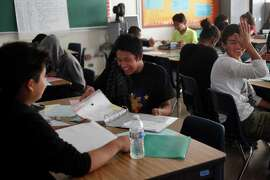 Byronne Rodrigo, 14 (center), jokes with friends Carlos Martinez, 14 (left), and Christian Moreno, 14, during geometry class Oct. 23, 2014, at Phillip and Sala Burton Academic High School in San Francisco. The Rodrigo family has been living in transitional housing for almost a year after staying with many family members in a small apartment. The family members haven't really had a place of their own and have enjoyed having the apartment to themselves but their time there is almost up. Byronne, the oldest of the three kids, has always helped out with his younger siblings, gets good grades in school and even had a skateboarding company sponsoring him for a while. He also has a job with a youth program that helps him pay for things he wants, like new skateboards.