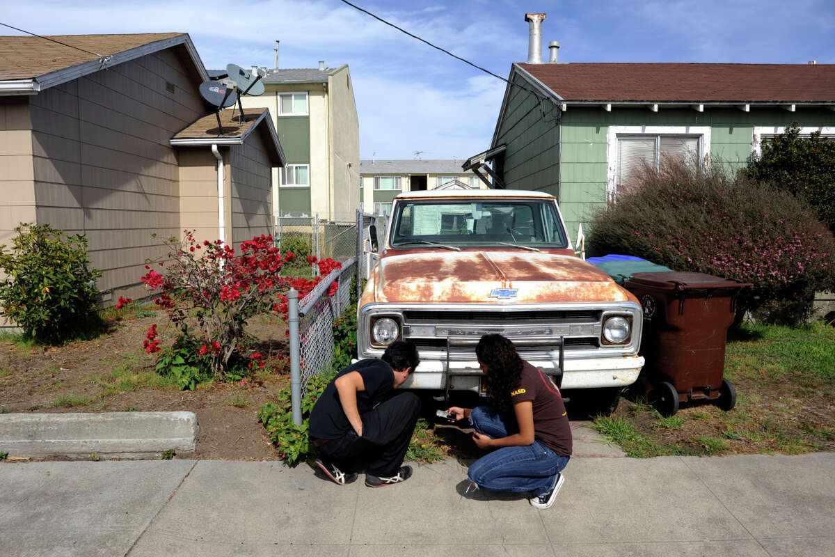 UC Berkeley students Danny De Santiago (left) and Laura Pérez Olivera search for edible plants near an old truck on an expedition in a residential section of Richmond.