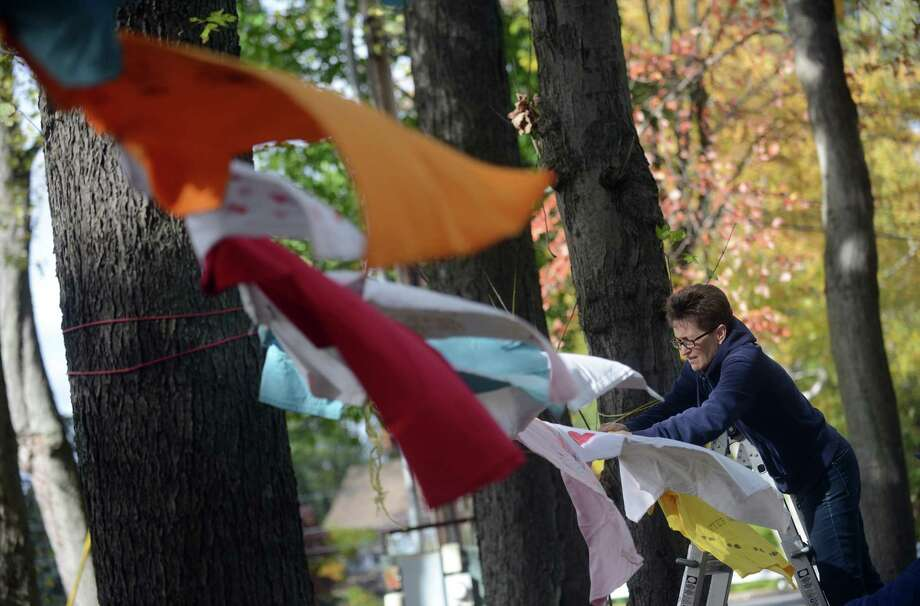 Nancy Stratford, of Trumbull, hangs T-shirts for the 7th Annual Clothesline Project Friday, Oct. 24, 2014 outside the Trumbull Library. Anyone affected by domestic violence or wanting to express support can decorate a shirt, available for free at the library circulation desk, and drop off or hang themselves on the lines in front of the library. The shirts will be on display through the end of the month. As part of the project, a vigil, sponsored by the Center for Family Justice, Trumbull Cares, Trumbull Library, Trumbull Rotary Club and Trumbull WomenâÄôs Club, will take place at the libary Tuesday, Oct. 28, 2014 at 6 p.m. at the Trumbull Library. Photo: Autumn Driscoll / Connecticut Post