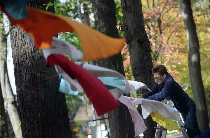 Nancy Stratford, of Trumbull, hangs T-shirts for the 7th Annual Clothesline Project Friday, Oct. 24,