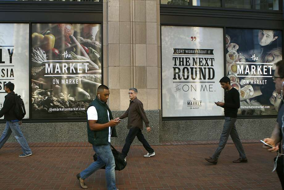 Pedestrians walk outside the new locally owned grocery store named Market on Market on the first floor of the Twitter building  in San Francisco, Calif., on Thursday, October 23, 2014.  Under construction Market on Market is scheduled to open by the holidays. Photo: Liz Hafalia, The Chronicle
