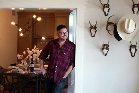 Morgan Weber, co-owner of Revival Market and Coltivare, stands near a display of roe deer antlers from Czechoslovakia that date back to the 1920s in his Heights bungalow. A cowboy hat hangs on turn-of-the-century South Texas white tail deer antlers on a pressed cast iron mount.