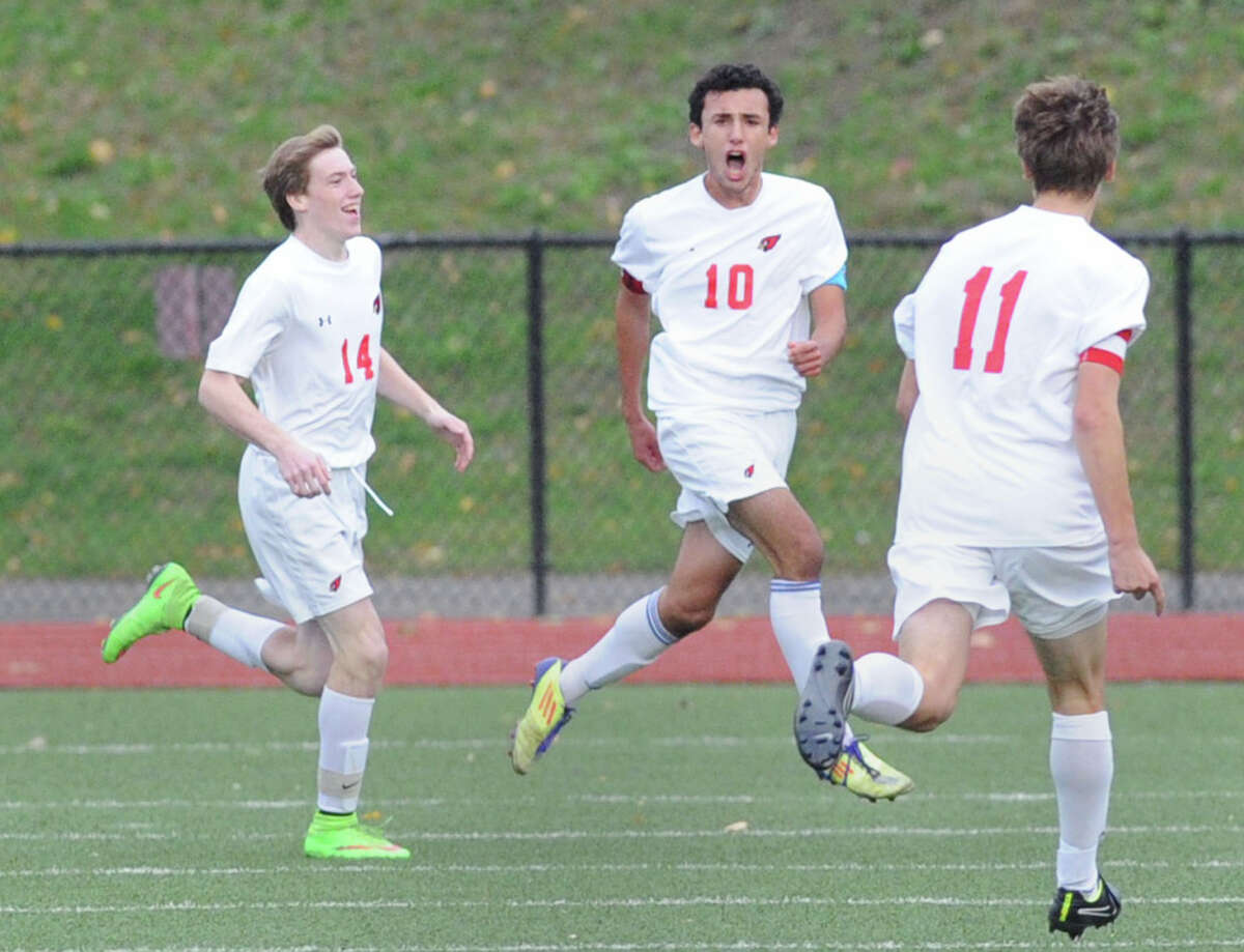 Paul Quiroga (#10) of Greenwich reacts after netting the third goal of the game during the boys high school FCIAC soccer quarterfinal match between Westhill High School and Greenwich High School at Greenwich, Conn., Friday afternoon, Oct. 24, 2014. Congratulating him are his Greenwich teammates, Liam Tracey (#14), left, and Daniel Ozizmir (#11). Greenwich advanced to the semifinal round with a 4-1 victory over Westhill.