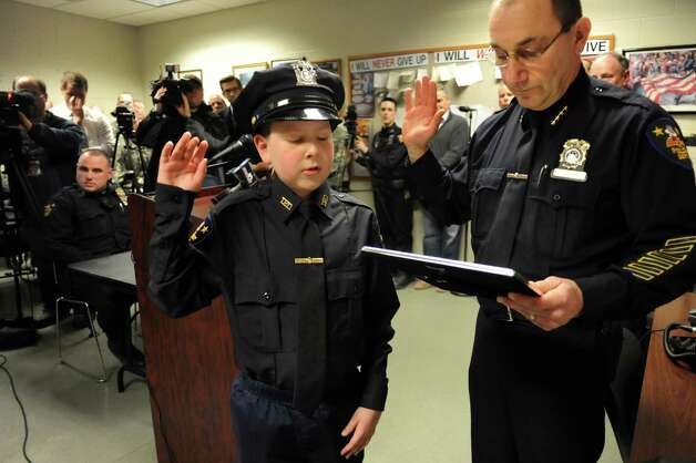J.P. Honsinger, 10, of Clifton Park, center, takes the oath of police officer from Chief John Tedesco on Friday, Jan. 31, 2014, at Troy Police Headquarters in Troy, N.Y. J.P., who has Niemann-Pick disease, was named an honorary member of the police force. (Cindy Schultz / Times Union archive) Photo: Cindy Schultz / 10025581A