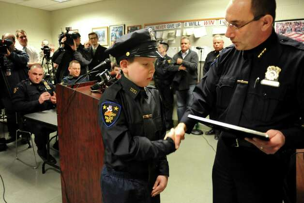 J.P. Honsinger, 10, of Clifton Park, center, shakes hands with Police Chief John Tedesco, after being sworn in on Friday, Jan. 31, 2014, at Troy Police Headquarters in Troy, N.Y. J.P., who has Niemann-Pick disease, was named an honorary member of the police force. (Cindy Schultz / Times Union) Photo: Cindy Schultz / 10025581A