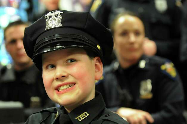 Honorary member J.P. Honsinger, 10, of Clifton Park, center, sits among fellow officers during roll on Friday, Jan. 31, 2014, at Troy Police Headquarters in Troy, N.Y. (Cindy Schultz / Times Union) Photo: Cindy Schultz / 10025581A