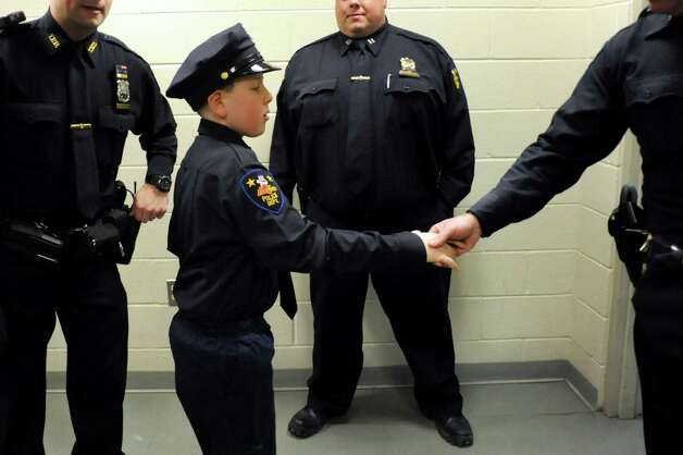 Honorary member J.P. Honsinger, 10, of Clifton Park, center, receives congratulations from fellow officers following his swearing in on Friday, Jan. 31, 2014, at Troy Police Headquarters in Troy, N.Y. (Cindy Schultz / Times Union) Photo: Cindy Schultz / 10025581A