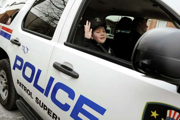 Honorary member J.P. Honsinger, 10, of Clifton Park gives a wave as he rides along with Officer Kyle Jones on Friday, Jan. 31, 2014, at Troy Police Headquarters in Troy, N.Y. (Cindy Schultz / Times Union) Photo: Cindy Schultz / 10025581A