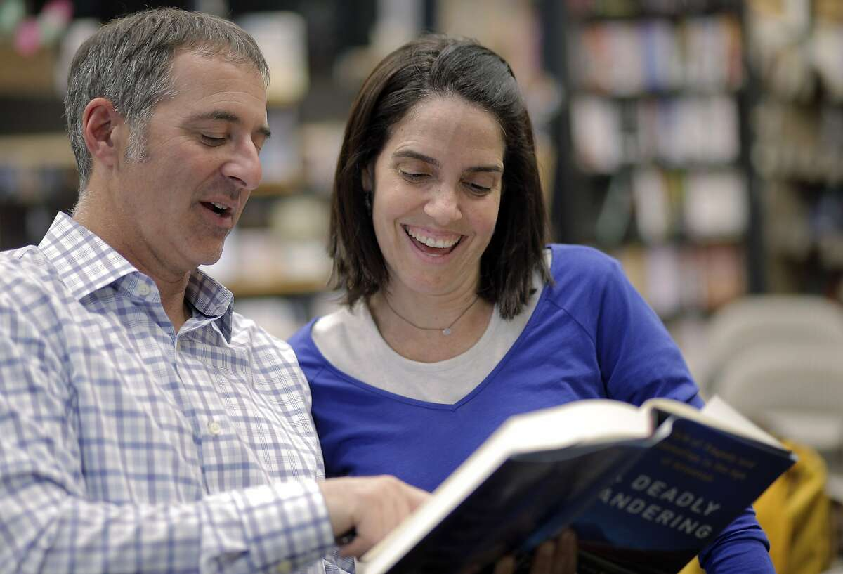 Matt Richtel, left, reads in inscription to Emily Roth of Palo Alto after a reading from his book,
