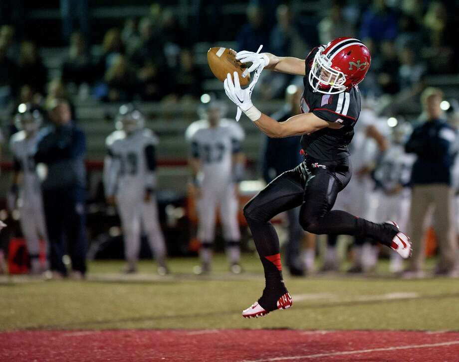 New Canaan's Michael Kraus makes a catch during Friday's football game against Staples at New Canaan High School on October 24, 2014. Photo: Lindsay Perry / Stamford Advocate