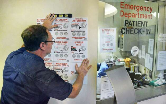 Ronald Chesky of St. Peter's facilities operations hangs a multilingual Ebola warning sign outside the hospital's emergency room Friday Oct. 24, 2014, in Albany, NY.  (John Carl D'Annibale / Times Union) Photo: John Carl D'Annibale