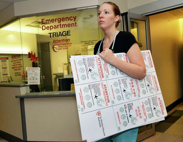 St. Peter's ER RN Belinda Camilleri facilities carries multilingual Ebola warning signs to be placed about the hospital's emergency room Friday Oct. 24, 2014, in Albany, NY.  (John Carl D'Annibale / Times Union) Photo: John Carl D'Annibale
