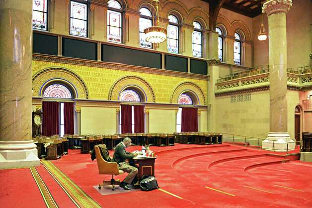 NYS State Assembly's sergeant-at-arms Wayne Jackson sits alone the Assembly Chamber after legislator's desks and chairs have been removed for a pre-season cleaning Friday Oct. 24, 2014, at the State Capitol in Albany, NY. (John Carl D'Annibale / Times Union) Photo: John Carl D'Annibale
