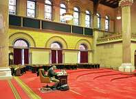 NYS State Assembly's sergeant-at-arms Wayne Jackson sits alone the Assembly Chamber after legislator's desks and chairs have been removed for a pre-season cleaning Friday Oct. 24, 2014, at the State Capitol in Albany, NY. (John Carl D'Annibale / Times Union)