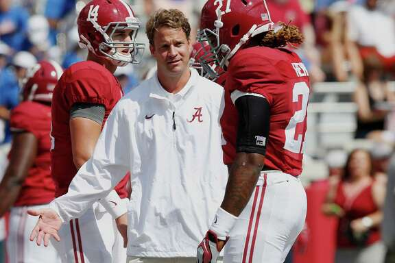 FILE - In this Sept. 20, 2014, file photo, Alabama offensive coordinator Lane Kiffin, center, talks to running back Derrick Henry (27) before an NCAA college football game against Florida in Tuscaloosa, Ala. Kiffin makes his return to Knoxville on Saturday, Oct. 25, 2014,  when the fourth-ranked Crimson Tide play the Volunteers. Kiffin coached at Tennessee for just one year before leaving for Southern California three weeks prior to National Signing Day. Although nearly five years have passed since Kiffin's hasty exit from Tennessee, Vols fans still haven't forgiven him. (AP Photo/Brynn Anderson, File)