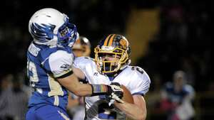 Newtown's Jaret Devellis (32) catches Brookfield's Andrew Collins (2) in the backfield for a loss during the Brookfield at Newtown High School boys football game, Friday night, October 24, 2014, in Newtown, Conn.