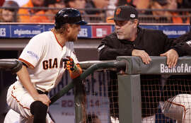 The Giants' Hunter Pence and manager Bruce Bochy talk in the dugout during Game 3 of the World Series at AT&T Park on Friday, Oct. 24, 2014.