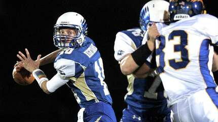 Newtown quarterback Jacob Burden (10) looks to pass while getting a block from team mate Peter Manfredonia (76) on Brookfield's Devan Joshi (83) during the Brookfield at Newtown High School boys football game, Friday night, October 24, 2014, in Newtown, Conn.