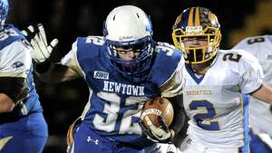 Newtown's Jaret Devellis (32) is wrapped up by Brookfield's Nick Acquantia (63) during the Brookfield at Newtown High School boys football game, Friday night, October 24, 2014, in Newtown, Conn. Brookfield's Andrew Collins (2) and Robert Drysdale are behind the play.
