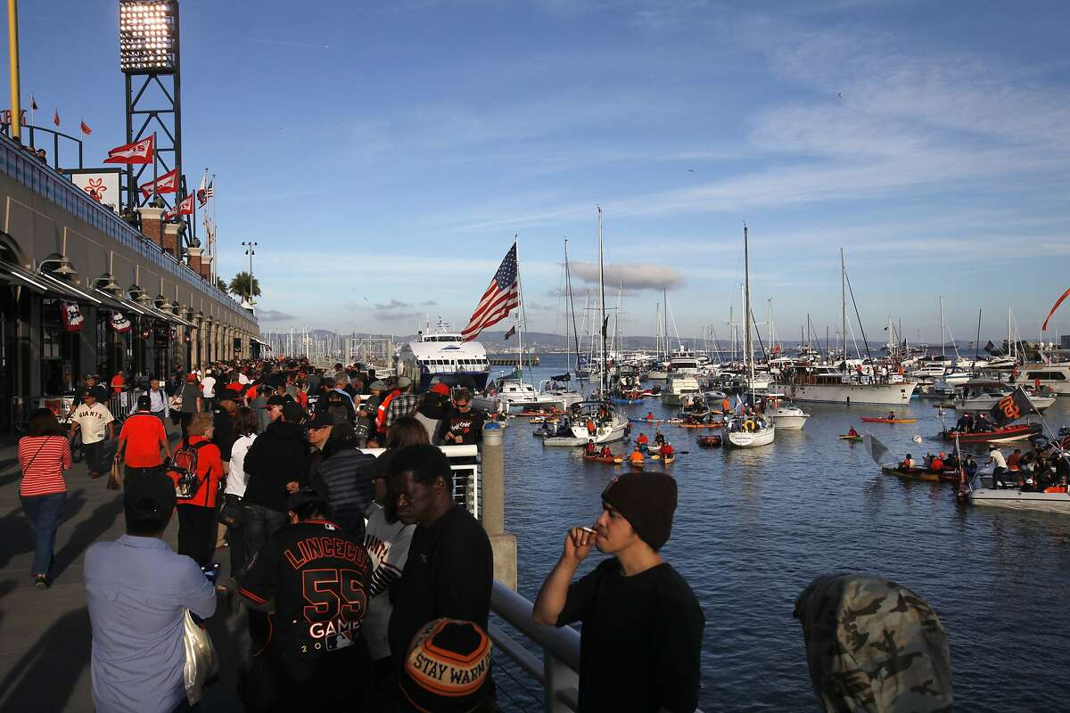 Grant Molino, center, takes a drag from his cigarette as fans gather in McCovey Cove outside of AT&T Park before Game 3 of the World Series between the Giants and the Royals Oct. 24, 2014 in San Francisco, Calif.