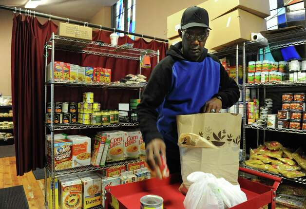 Volunteer Dwight Smith of Albany fills an order at the FOCUS interfaith food pantry in FOCUS Churches of Albany which is housed in Emmanuel Baptist Church on Tuesday, Oct. 22, 2013 in Albany, N.Y.  FOCUS and the Hunger Action Network of New York State are holding an Empty Bowls Anti-Hunger Benefit on Thursday evening at The Linda. (Lori Van Buren / Times Union) Photo: Lori Van Buren / 00024313A