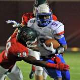 Oak Ridge Kwame Etwi (9) is tackled by The Woodlands defensive back Talon Baskin during the first half of a high school football game, Friday, October 24, 2014, at Woodforest Stadium in Shenandoah.