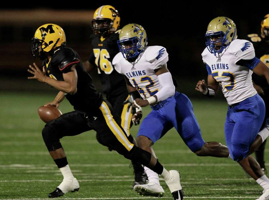 Marshall quarterback Jeremy Smith scrambles as he is pursued by Elskins' Leroy Godfrey (42) during a high school football game between Elkins and Fort Bend Marshall at Hall Stadium, Friday, Oct. 24, 2014. (Bob Levey/For The Chronicle) Photo: Bob Levey, Houston Chronicle / ©2014 Bob Levey