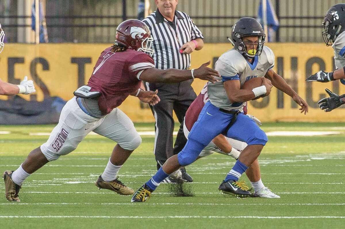 Clear Springs #5 Matthew Guidry tries to scramble away from the Clear Creek defense during the game at Veterans Memorial Stadium 10/23/14