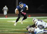 La Salle's Joe Germinerio jumps over Saratoga defenders on his way to a touchdown run during their Class AA quarterfinal high school football game on Friday Oct. 24, 2014 in Watervliet, N.Y.  (Michael P. Farrell/Times Union)