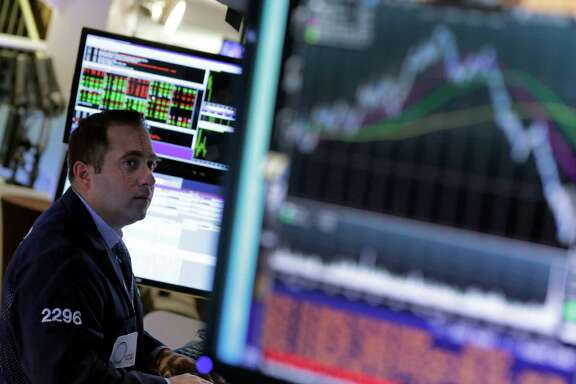 FILE - In this Wednesday, Oct. 22, 2014, file photo, a specialist works at his post on the floor of the New York Stock Exchange. The market's flux over the past week has given investors pause for thought. (AP Photo/Richard Drew, File)
