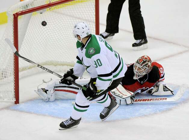 Dallas Stars' Jason Spezza (90) scores a goal against New Jersey Devils goaltender Cory Schneider during a shootout t an NHL hockey game Friday, Oct. 24, 2014, in Newark, N.J. The Stars won 3-2. (AP Photo/Bill Kostroun) ORG XMIT: NJBK106 Photo: Bill Kostroun / FR51951 AP