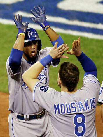 Kansas City Royals' Alcides Escobar is congratulated by teammate Mike Moustakas after scoring during the sixth inning of Game 3 of baseball's World Series against the San Francisco Giants Friday, Oct. 24, 2014, in San Francisco. (AP Photo/Eric Risberg)  ORG XMIT: WS335 Photo: Eric Risberg / AP