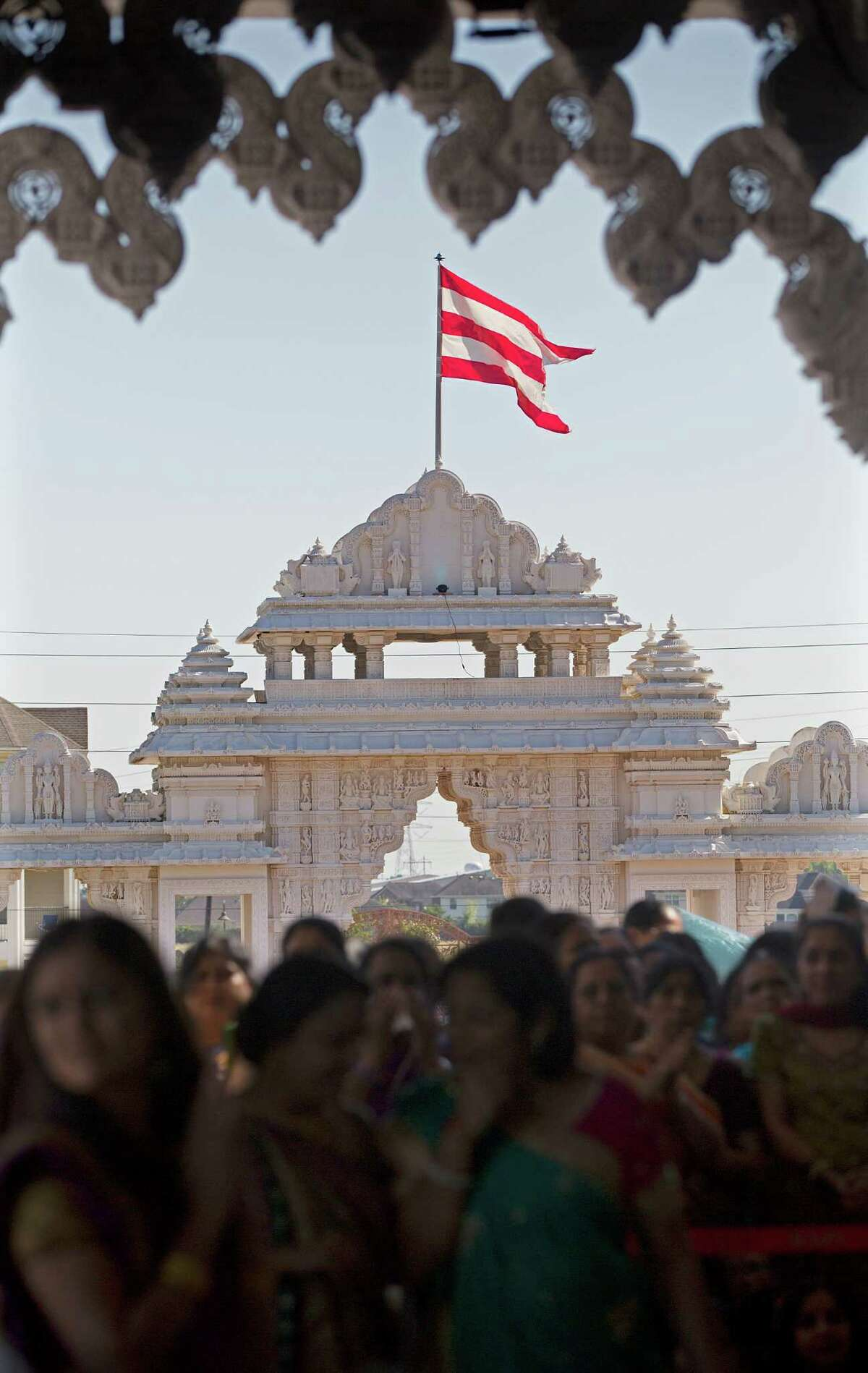 The BAPS flag waves in the background as worshipers offer their prayers, songs and chants to usher in the Hindu New Year during Annakoot celebrations, the day after Diwali at the BAPS Shri Swaminarayan Mandir Friday, Oct. 24, 2014, in Stafford.