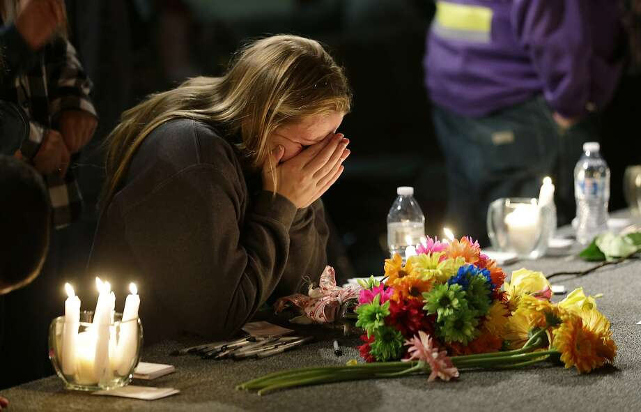 A young woman holds her head in her hands as she kneels before candles and flowers placed on the stage at the Grove Church in Marysville, Wash., Friday, Oct. 24, 2014, after a memorial vigil held for people affected by a shooting at Marysville Pilchuck High School earlier in the day. (AP Photo/Ted S. Warren) Photo: Ted S. Warren, Associated Press